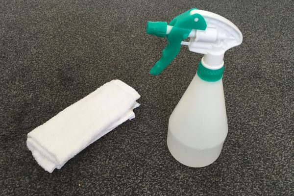 Spray bottle and white cloth to aid stain/spill removal on grey carpet